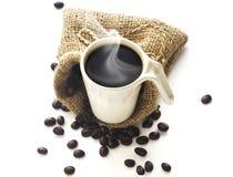 Taza de café y granos de café en fondo del blanco del saco Fotos de archivo