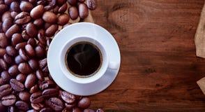 Taza de caf? y granos de caf? en el estilo de madera del vintage del fondo de la tabla para el dise?o gr?fico fotos de archivo