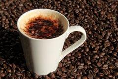 Taza de cappuccino con los granos de café Fotos de archivo libres de regalías