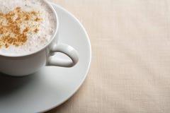 Taza de cappuccino sobre el fondo de lino Fotografía de archivo libre de regalías