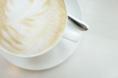Taza de Cappucino en la tabla blanca Fotos de archivo libres de regalías