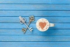 Taza de capuchino con símbolo de la forma del corazón y dos llaves Imagen de archivo libre de regalías