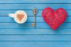 Taza de capuchino con símbolo, llave y el juguete de la forma del corazón Imágenes de archivo libres de regalías