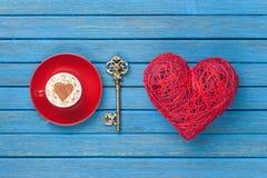 Taza de capuchino con símbolo, llave y el juguete de la forma del corazón Fotos de archivo