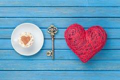 Taza de capuchino con símbolo, llave y el juguete de la forma del corazón Fotografía de archivo libre de regalías