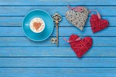 Taza de capuchino con símbolo, llave y los juguetes de la forma del corazón Imágenes de archivo libres de regalías