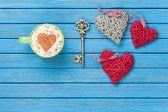 Taza de capuchino con símbolo, llave y los juguetes de la forma del corazón Foto de archivo libre de regalías