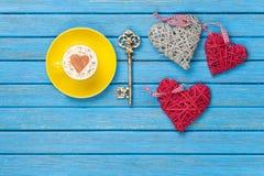 Taza de capuchino con símbolo, llave y los juguetes de la forma del corazón Fotografía de archivo