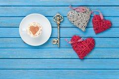 Taza de capuchino con símbolo, llave y los juguetes de la forma del corazón Fotos de archivo