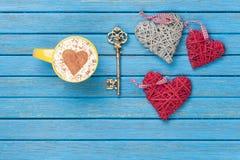 Taza de capuchino con símbolo, llave y los juguetes de la forma del corazón Imagen de archivo libre de regalías