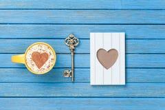 Taza de capuchino con símbolo, llave y los juguetes de la forma del corazón Imagenes de archivo