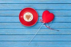 Taza de capuchino con símbolo y el juguete de la forma del corazón Imagen de archivo