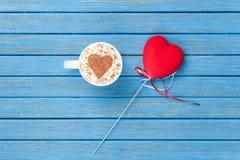 Taza de capuchino con símbolo y el juguete de la forma del corazón Imagenes de archivo