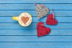 Taza de capuchino con símbolo y los juguetes de la forma del corazón Foto de archivo libre de regalías