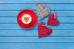 Taza de capuchino con símbolo y los juguetes de la forma del corazón Foto de archivo