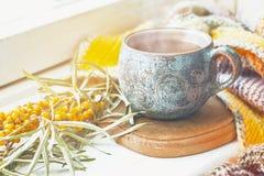 Taza de cerámica con té, rama de espino amarillo y una manta hecha punto Fotografía de archivo libre de regalías