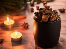 Taza de cerámica negra con canela en la tabla de madera oscura con las velas Fotos de archivo libres de regalías