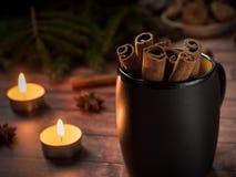 Taza de cerámica negra con canela en la tabla de madera oscura con las velas Imagenes de archivo
