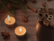 Taza de cerámica negra con canela en la tabla de madera oscura con las velas Fotos de archivo
