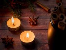 Taza de cerámica negra con canela en la tabla de madera oscura con las velas Foto de archivo