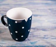Taza de cerámica negra quebrada, fondo de madera azul, espacio libre foto de archivo libre de regalías