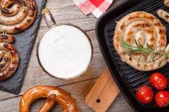 Taza de cerveza, camarones asados a la parrilla, salchichas y pretzel Foto de archivo