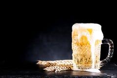 Taza de cerveza con espuma imágenes de archivo libres de regalías