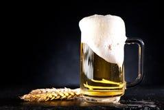 Taza de cerveza con espuma imagen de archivo