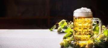 Taza de cerveza con espuma en la tabla con los saltos en el fondo oscuro, vista delantera Fotos de archivo