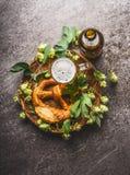 Taza de cerveza con la botella, el pretzel y los saltos en fondo rústico oscuro Fotos de archivo