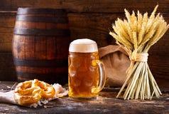 Taza de cerveza con los oídos y el pretzel del trigo Imagen de archivo