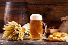 Taza de cerveza con los oídos y el pretzel del trigo Foto de archivo