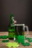 Taza de cerveza, de botella de cerveza y de tréboles verdes para el día del St Patricks Fotografía de archivo libre de regalías