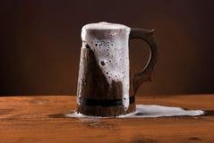 Taza de cerveza de madera con espuma. Foto de archivo libre de regalías