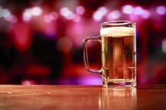 Taza de cerveza deliciosa en una barra Imagenes de archivo