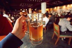 Taza de cerveza a disposición de visitante del Biere popular Brewing Company y club Imagen de archivo libre de regalías