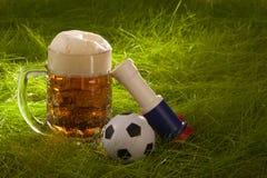 Taza de cerveza dorada fresca, de vuvuzela y de pequeño balón de fútbol en la hierba. Fotografía de archivo