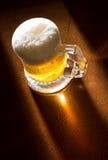 Taza de cerveza en el vector de madera Fotografía de archivo libre de regalías
