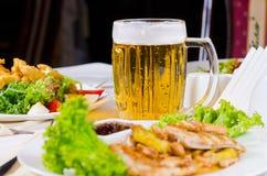 Taza de cerveza en la tabla con los platos plateados de la comida Imagen de archivo