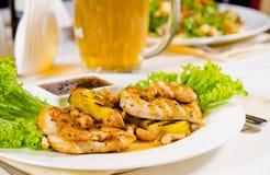 Taza de cerveza en la tabla del restaurante con la comida plateada Foto de archivo libre de regalías