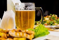 Taza de cerveza en la tabla del restaurante con la comida plateada Fotos de archivo