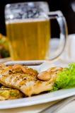 Taza de cerveza en la tabla del restaurante con la comida plateada Imagenes de archivo