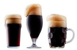 Taza de cerveza oscura escarchada con espuma Foto de archivo