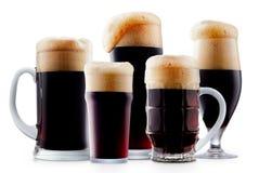 Taza de cerveza oscura escarchada con espuma Fotos de archivo libres de regalías