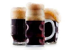 Taza de cerveza oscura escarchada con espuma Fotos de archivo