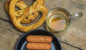 Taza de cerveza, pretzeles, y salchichas Foto de archivo libre de regalías