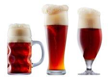 Taza de cerveza rojo oscuro escarchada con espuma Foto de archivo libre de regalías
