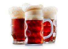 Taza de cerveza rojo oscuro escarchada con espuma Imagen de archivo libre de regalías