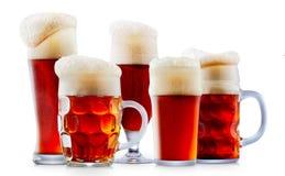 Taza de cerveza rojo oscuro escarchada con espuma Fotos de archivo