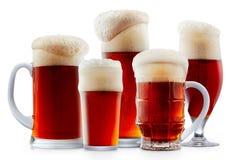 Taza de cerveza rojo oscuro escarchada con espuma Fotografía de archivo libre de regalías